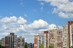 Apartment buildings under blue sky. European apartment buildings standing under blue sky with summer white clouds Royalty Free Stock Photo