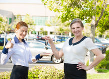 Apartment, car sale. Salesperson passing keys to customer. Portrait two happy, excited business women one giving to customer car or home keys, isolated outdoors Stock Image