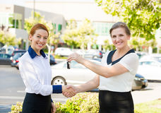 Apartment, car sale. Salesperson passing keys to customer. Portrait two happy, excited business women one giving to customer car or home keys,  outdoors Royalty Free Stock Photography