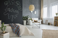 Apartment with chalkboard and bed. Grey apartment with bed, chalkboard, cactus, table, lamp and sofa stock photography