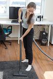 Apartment cleaning.A young European girl vacuuming a room. Apartment cleaning.A young European girl with long hair vacuuming a room Stock Photos