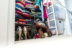 Real apartment closet organized and filled with woman`s clothes, depicting shopping, lifestyle habits, real life and clothing. Apartment closet organized and stock images