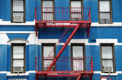 Apartment facade with red fire escape Stock Photo