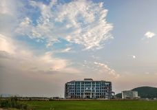 A large building with amazing clouds and mountains in the background. Apartment in a field with green grass stock photo
