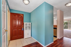 Apartment hallway interior with blue walls, tile and wood flooring. Royalty Free Stock Photography