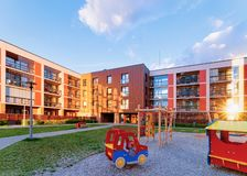 Apartment house and home buildings complex concept playground sun light. Apartment house and home buildings complex concept. Street with children playground stock photo