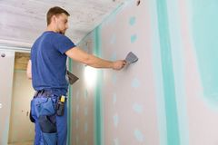 Apartment interior construction - worker plastering gypsum board. Wall royalty free stock images