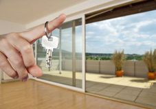 Apartment and key. Hand holding a key in front of a apartment Royalty Free Stock Photos