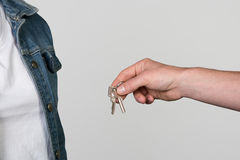 Apartment Key handover to a woman, isolated on grey. Royalty Free Stock Images