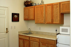 Apartment Kitchen. Kitchen area of apartmetn with wood cabinets, stainless steel sink, and fridge with microwave Royalty Free Stock Images