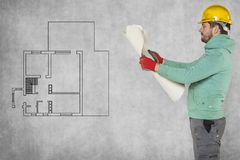 Apartment layout, a challenge for the worker. Protective helmet on the head Royalty Free Stock Images