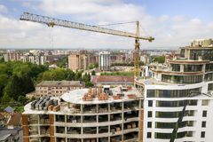 Apartment or office tall building under construction. Brick walls, glass windows, scaffolding and concrete support pillars. Tower royalty free stock images