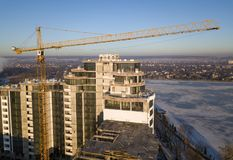 Apartment or office tall building under construction, top view. Tower crane on bright blue sky copy space background, city. Landscape stretching to horizon stock image