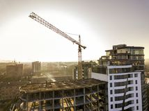 Apartment or office tall building under construction, top view. Tower crane and city landscape stretching to horizon. Drone aerial. Photography stock photo