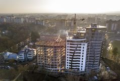 Apartment or office tall building under construction, top view. Tower crane and city landscape stretching to horizon. Drone aerial. Photography royalty free stock image