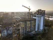 Apartment or office tall building under construction, top view. Tower crane and city landscape stretching to horizon. Drone aerial stock photography