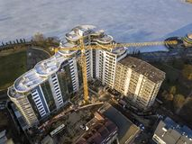 Apartment or office tall building under construction, top view. Tower crane and city landscape stretching to horizon. Drone aerial. Photography royalty free stock images