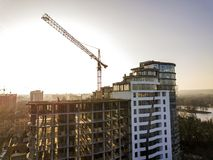 Apartment or office tall building under construction, top view. Tower crane and city landscape stretching to horizon. Drone aerial. Photography stock photos