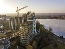 Apartment or office tall building under construction, top view. Tower crane and city landscape stretching to horizon. Drone aerial. Photography royalty free stock photos
