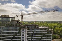 Apartment or office tall building unfinished under construction among green tree tops. Tower cranes on bright blue sky copy space stock photos