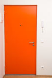 Apartment orange door over white wall Royalty Free Stock Image
