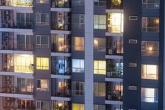 Apartment privacy concept at night with lighting and electricity use rising yearly. Apartment windows at night. Windows lit royalty free stock photo