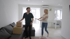 Apartment purchase, cheerful couple bring boxes and delight buying new housing during housewarming and improvement. Apartment purchase, cheerful couple bring stock video