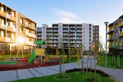 Apartment residential house facade architecture with children playground sun light. Apartment residential house facade architecture with children playground and royalty free stock photo