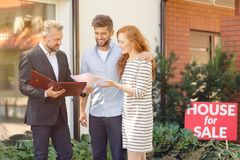 Apartment seller presenting buying conditions. Seller of apartment presenting conditions for buying property to smiling couple royalty free stock images