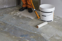 Apartment under construction. Worker puts primer with roller on Stock Images