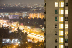 Apartment windows at night with the Asian cityscape of Bangkok in the background. Traffic and the thriving pulse of the city can b Royalty Free Stock Photography