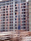 Apartments building under construction with crane and steel fittings near royalty free stock photos
