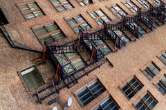 Apartments and fire escape. Long fire escape on the side of an aging brick apartment building shot diagonally across the frame Stock Photos