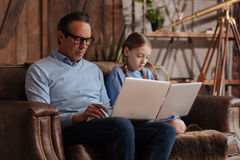 Apathetic family surfing the Internet at home. Trapped in social Internet life . Elderly involved ignorant grandfather sitting at home and using laptops with Royalty Free Stock Images