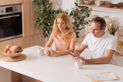 Apathetic mature couple starring at smartphones at home. Incurious to our relationships. Addicted incurious involved couple sitting at home and using smartphones Royalty Free Stock Image
