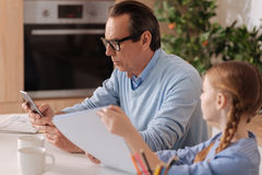 Apathetic pensioner ignoring kid at home. Real world indifferent. Involved indifferent elderly men using digital device at home and ignoring child while surfing Stock Images