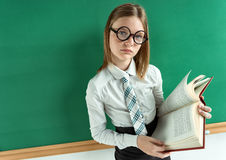 Apathetic student with book near the blackboard Royalty Free Stock Photos