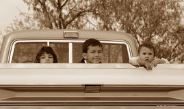 Apathy Kids. Three Hispanic American children, each with their own possibly bored expression, in the back of a classic pick up truck. Sepia toned for effect Stock Images