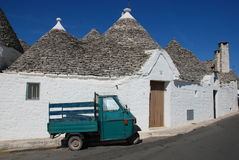 Ape in Alberobello. A small green ape parked outside some trulli houses in the southern Italian city of Alberobello stock images