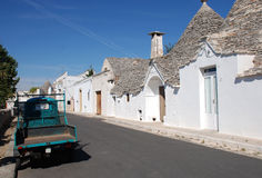 Ape on Street of Trulli. A small green ape parked outside some trulli houses in the southern Italian city of Alberobello royalty free stock photos