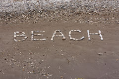 Apedreja o fundo do mar na areia molhada da praia Fotografia de Stock Royalty Free