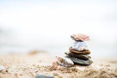 Apedreja a pirâmide na areia Mar no fundo Fotografia de Stock