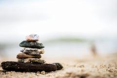 Apedreja a pirâmide na areia Mar no fundo Imagem de Stock
