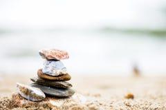 Apedreja a pirâmide na areia Mar no fundo Imagem de Stock Royalty Free