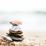 Apedreja a pirâmide na areia Mar no fundo Imagens de Stock