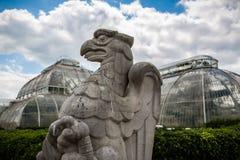 Apedreje a estátua cinzelada da águia na frente das grandes casas verdes de vidro em Kew, Londres, Reino Unido fotografia de stock