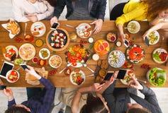 Apego del dispositivo del artilugio, cena de los amigos con los smarphones foto de archivo