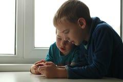 Apego do jogo nas crianças duas crianças que jogam com um smartphone ao sentar-se em casa na tabela fotografia de stock