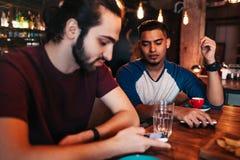 Apego social de la red Dos amigos de la raza mixta que usan smartphones en restaurante en vez de la comunicación Foto de archivo