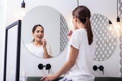 Apelando os dentes de escovadela da mulher na frente do espelho circular fotos de stock royalty free